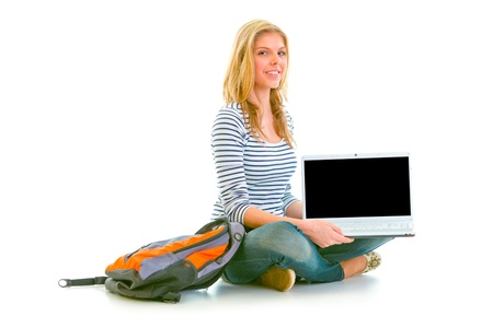 Smiling teen girl sitting on floor and showing laptops blank screen isolated on white   photo