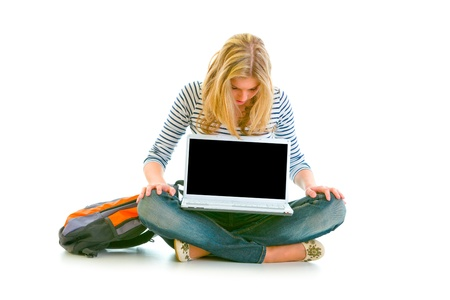 Teen girl sitting on floor and looking on laptops blank screen isolated on white Stock Photo - 10344768