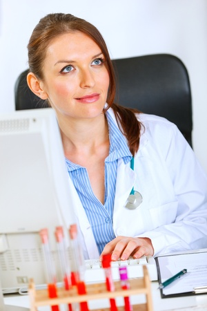 stargaze: Pretty medical doctor woman sitting at office table and dreaming