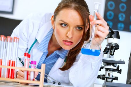 medical test: Thoughtful medical doctor woman in laboratory analyzing results of medical test