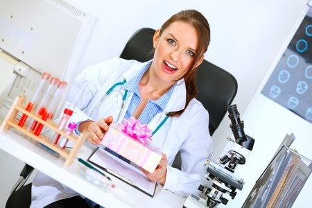 doctor holding gift: Surprised medical doctor woman sitting at office table and holding gift in hands