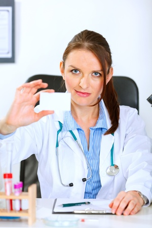 authoritative: Authoritative medical doctor woman sitting at office table and holding blank business card