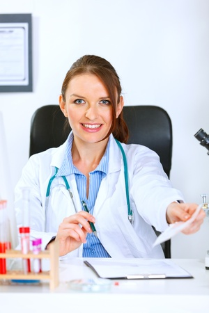 Smiling medical doctor woman sitting at table and giving medical prescription  photo