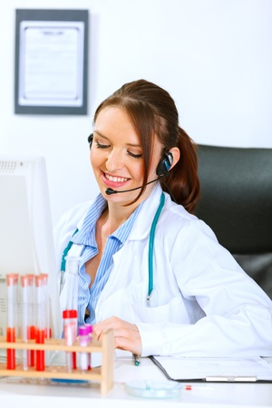Smiling medical doctor woman with headset sitting at office table and talking with someone  photo