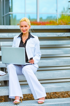 Happy modern business woman sitting on stairs at office building and working on laptop  photo