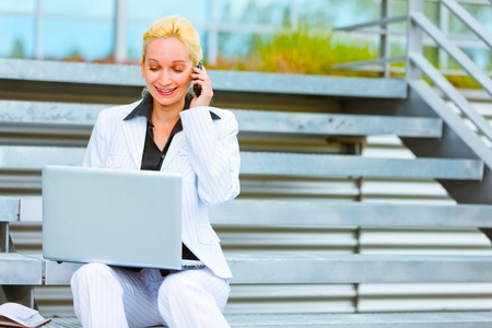 Smiling modern business woman sitting on stairs talking on mobile and looking in laptop   photo