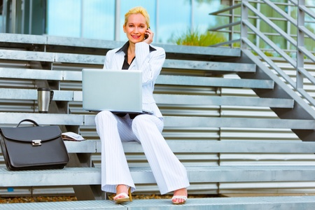 Smiling modern business woman sitting on stairs with laptop and talking on cell phone  photo
