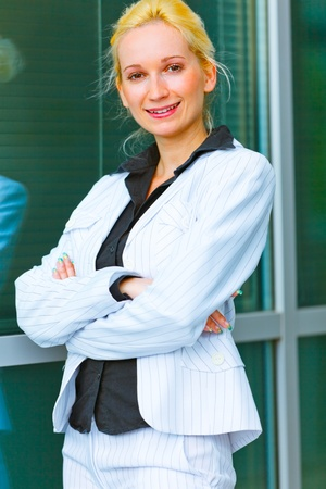 Smiling modern business woman standing near office building   photo