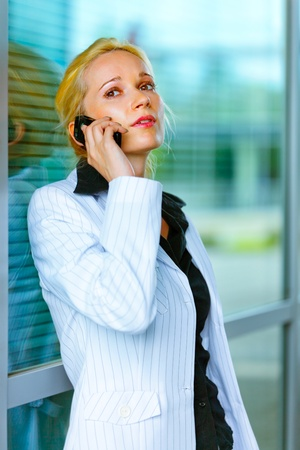 centrality: Concentrated modern business woman talking on mobile at office building   Stock Photo