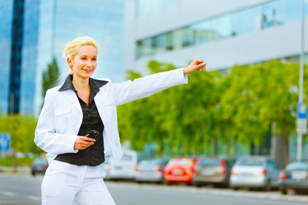 catching taxi: Smiling modern business woman catching taxi near office center  Stock Photo
