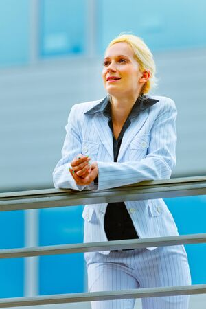 sagacious: Pensive modern business woman leaning on railing at office building looking in corner  Stock Photo