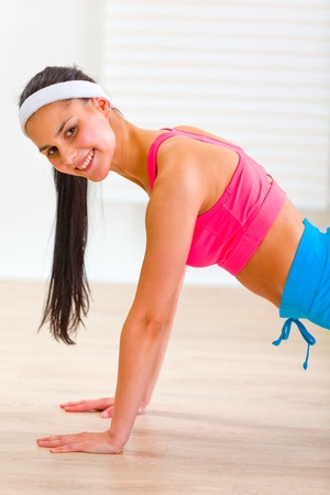 Smiling flexible pretty girl making push-up exercises  photo