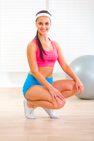 squatting down: Smiling fit pretty girl squatting down  Stock Photo