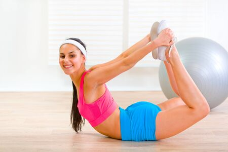 Smiling flexible girl making gymnastics exercise at home  photo