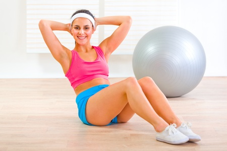 Happy  fitness girl doing abdominal crunch on floor at home  photo
