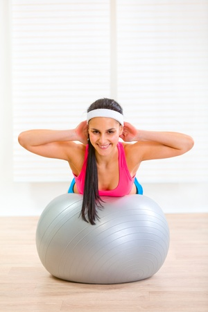 Happy fitness girl doing abdominal crunch on fitness ball at home  photo
