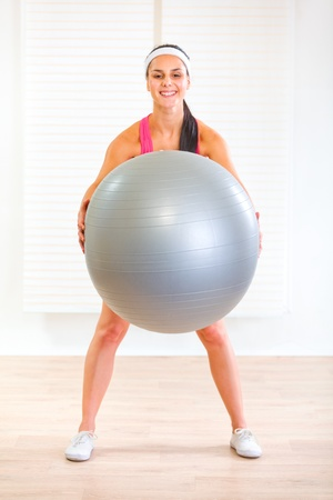 Happy healthy girl doing exercises with fitness ball at home  photo