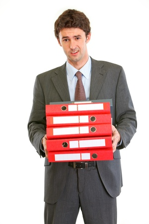 displeased businessman: Displeased modern businessman holding many folders isolated on white  Stock Photo