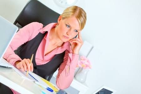 sagacious: Modern business woman sitting at office desk and thinking   Stock Photo