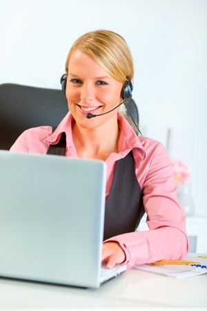 Smiling modern business woman with headset working on laptop  photo