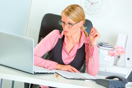 sagacious: Modern business woman in eye glasses working on laptop  Stock Photo