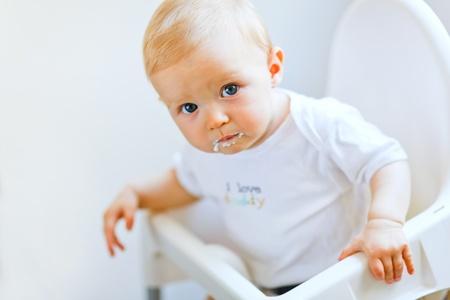 smeared baby: Comer a ni�a bonita borrosos en comer de silla de beb�   Foto de archivo
