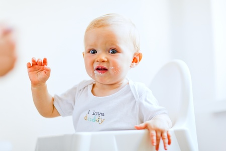 eat smeared: Eat smeared adorable baby girl in baby chair sighing