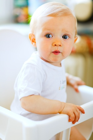 Eat smeared pretty baby girl in baby chair interestedly looking