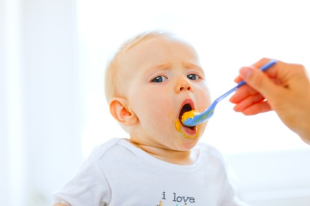 baby chair: Eat smeared pretty baby girl open mouth for spoon  Stock Photo