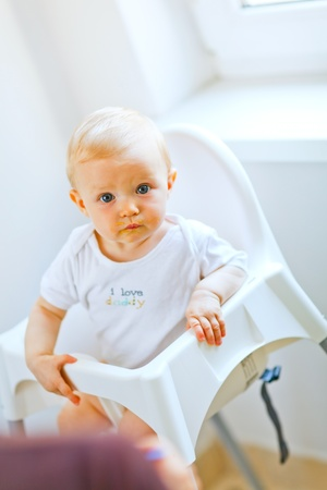 Eat smeared adorable baby girl in baby chair interestedly looking Stock Photo - 10716346