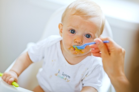 Eat smeared pretty baby girl eating from spoon Stock Photo - 10716411