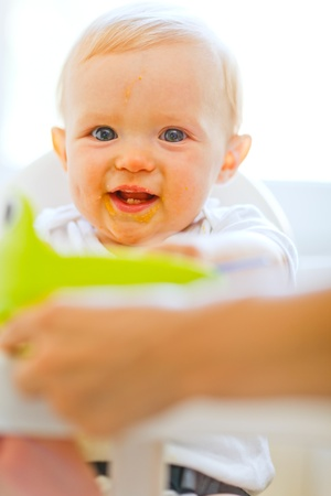 Eat smeared smiling baby sitting in baby chair
