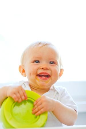 smeared baby: Coma beb� manchado sonriendo jugando con la placa