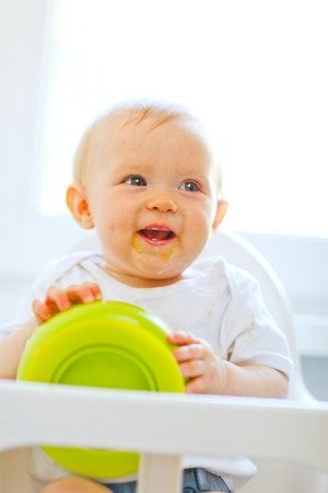 Eat smeared cheerful baby  in baby chair playing with plate Stock Photo - 10716358
