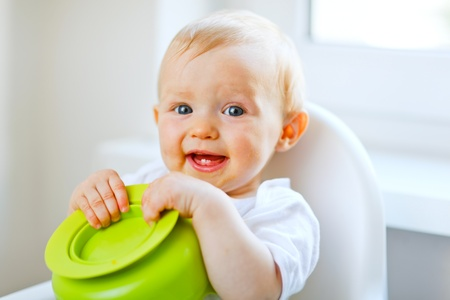 baby on chair: Adorable baby sitting in baby chair and playing with plate
