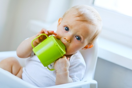 Lovely baby  sitting in chair and drinking from baby cup  Stock Photo