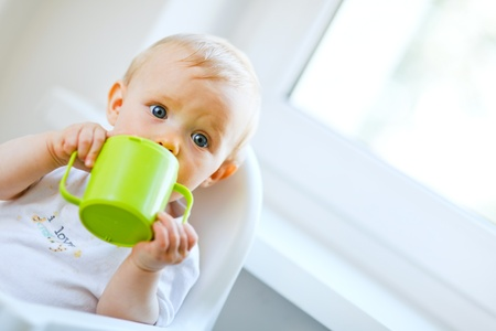 baby on chair: Pretty baby  sitting in chair and drinking from baby cup