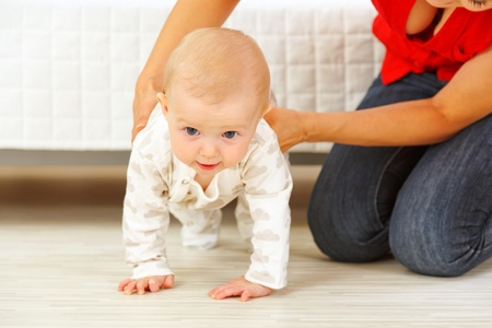 to creep: Mother helping cheerful baby learn to creep  Stock Photo