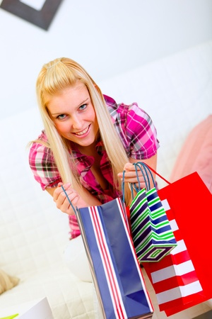 Smiling woman sitting on sofa and holding shopping bags in hands  photo