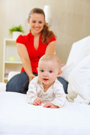 Smiling mother and adorable baby playing on sofa