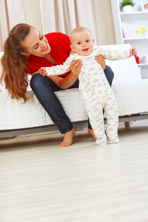 Smiling mother helping cheerful baby learn to walk Stock Photo - 10843981