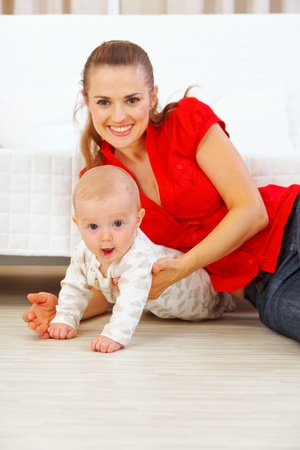 baby playing: Happy mother and lovely baby playing on floor  Stock Photo