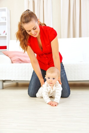 to creep: Smiling mother helping cheerful baby learn to creep  Stock Photo
