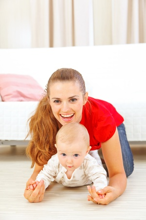 baby playing: Smiling mommy and adorable baby playing on floor