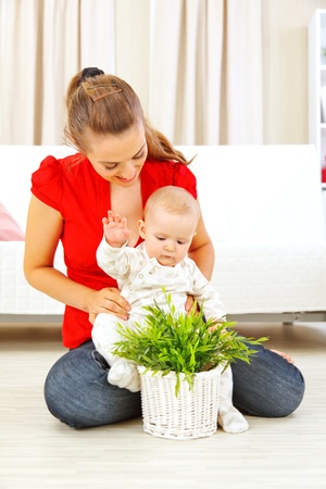 interrogatively: Smiling mommy showing plant to her baby