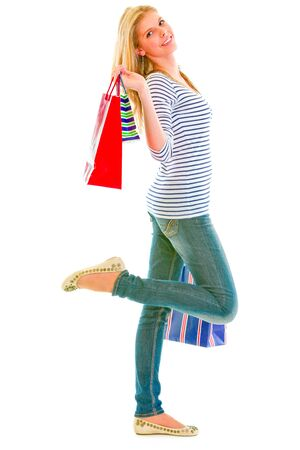 Happy teen girl with shopping bags isolated on white 