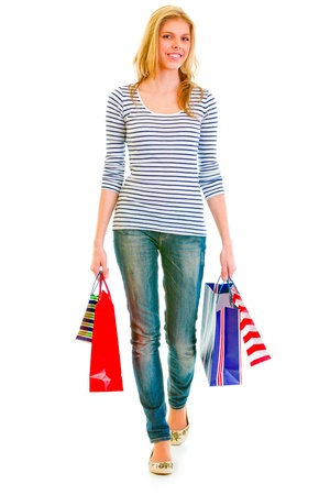 Smiling teen girl with shopping bags making step isolated on white   photo