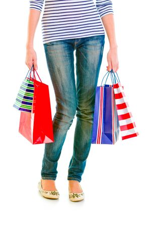 Closeup on shopping bags in hands near legs isolated on white 