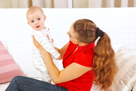 interrogatively: Mother sitting on divan and holding intersted baby in hands  Stock Photo
