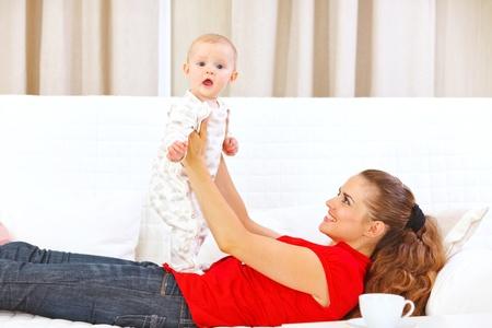 divan: Madre sonriente y adorable beb� jugando en sof� Foto de archivo